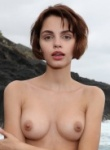 Ariela in her mellow yellow bikini on the rocks as the waves crash behind her she strips off to reveal her nude body